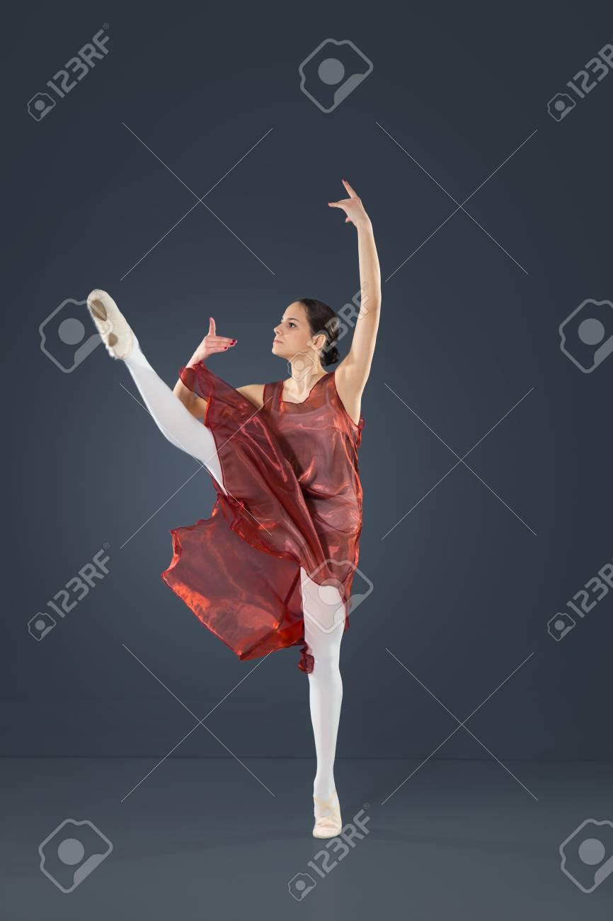Hermosa bailarina de ballet femenino sobre un fondo gris. La bailarina está vestido con un tutú y zapatos de punto.