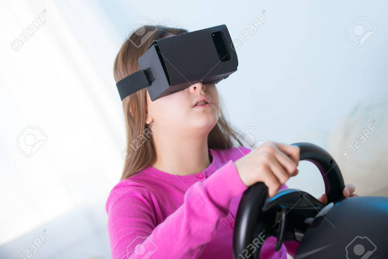 b3239f0dfa9 Happy smiling young beautiful young girl holding a gaming computer wheel  getting experience using VR-