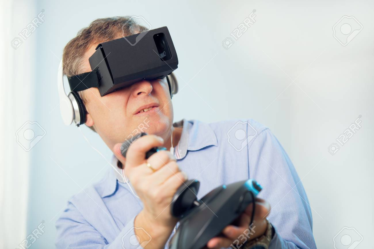 13b9f096150 Man holding a gaming computer wheel getting experience using VR-headset  glasses of virtual reality