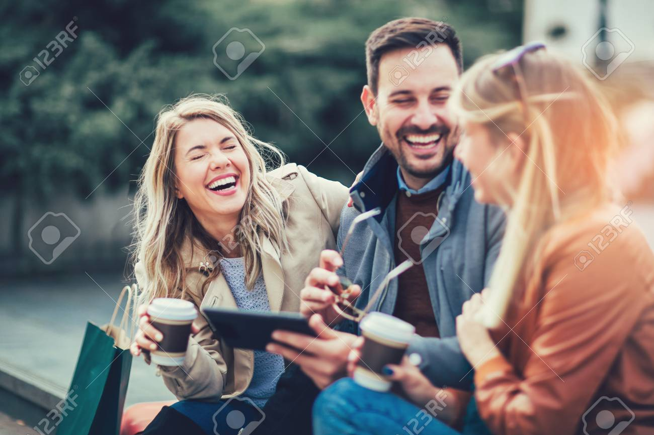Group of smiling friends with digital tablet outdoor - 121110324