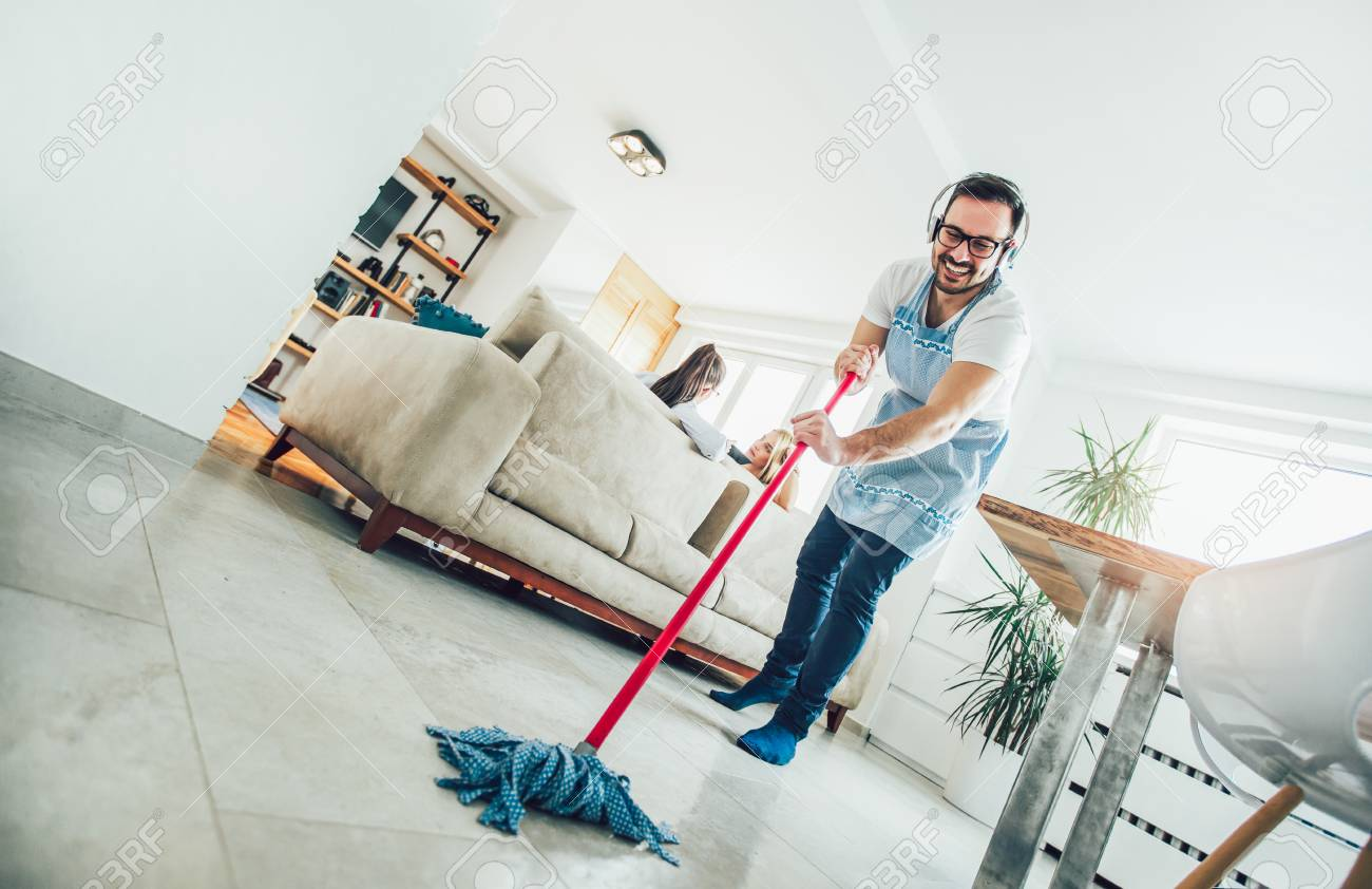 Husband housekeeping and cleaning concept. A man cleans the house, while women gossiping on the sofa - 121110942