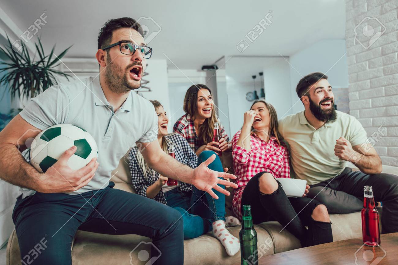 Happy friends or football fans watching soccer on tv and celebrating victory at home.Friendship, sports and entertainment concept. - 94809031