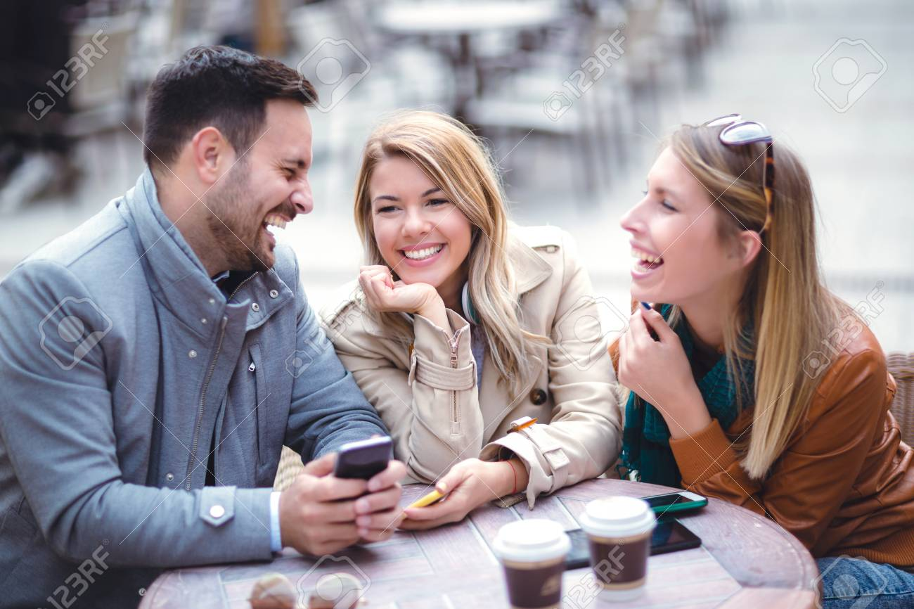 Group Of Three Friends Using Phone In Outdoor Cafe On Sunny Day Stock Photo Picture And Royalty Free Image Image 97377872