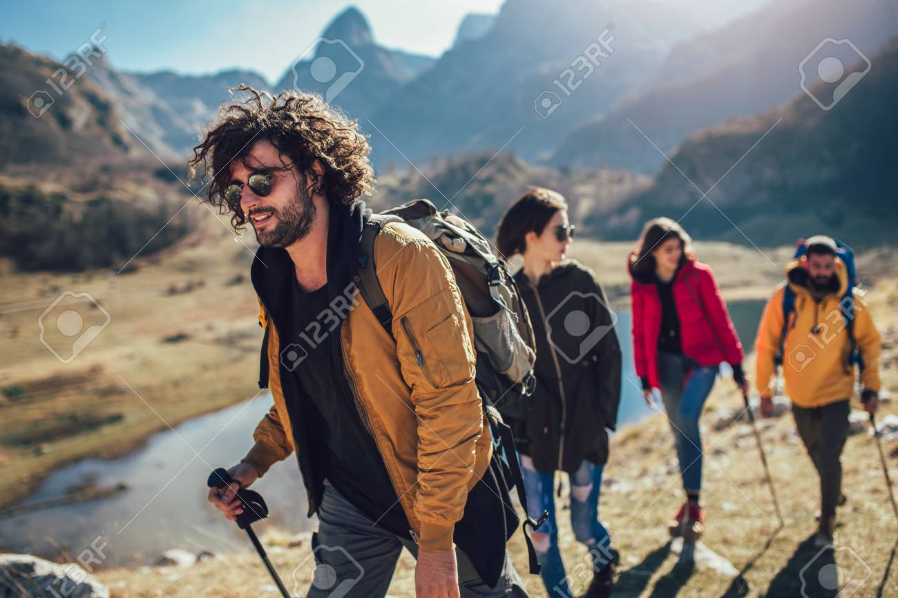 Group of hikers walking on a mountain at autumn day - 119719370