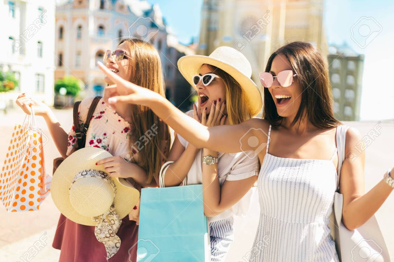 Three beautiful girls in sunglasses with shopping bags in city. - 128614538
