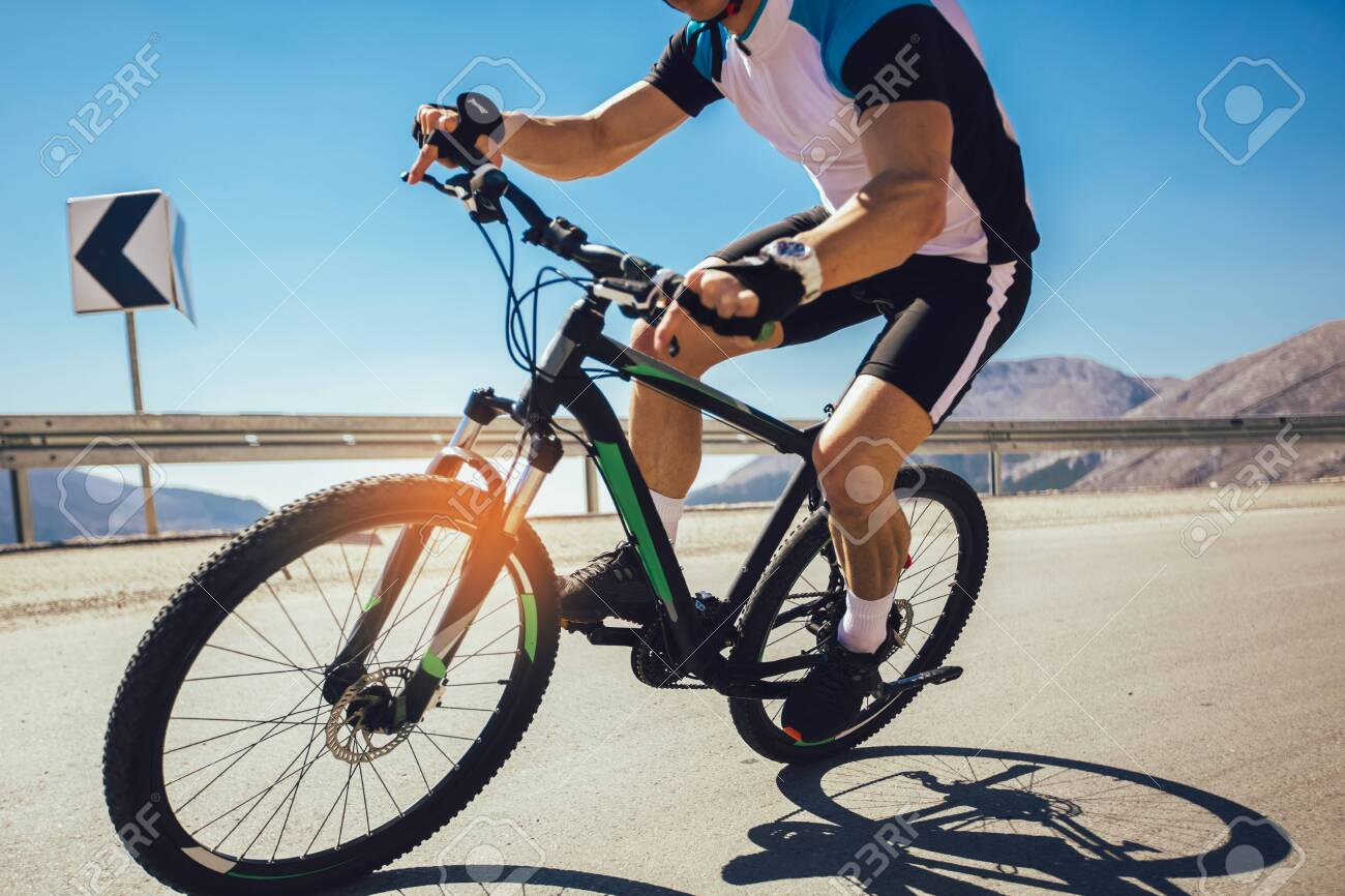 Man ride mountain bike on the road. Sport and active life concept. - 129739626