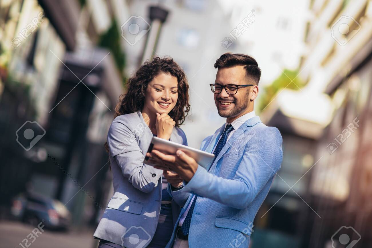Handsome man and beautiful woman as business partners using digital tablet outdoor - 130113874