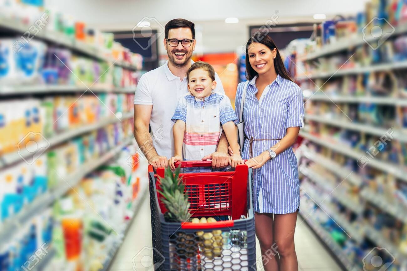 Happy family with child and shopping cart buying food at grocery store or supermarket - 130636737