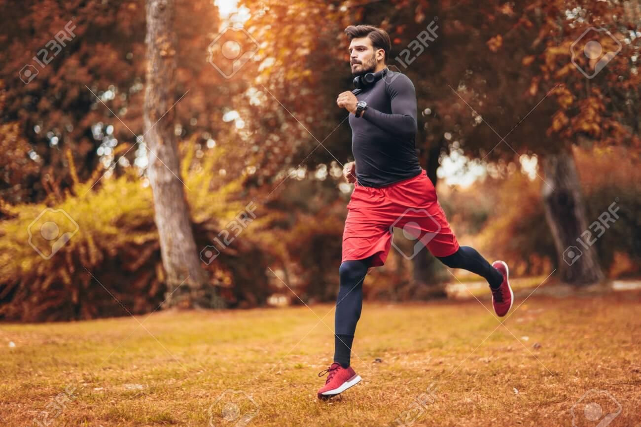 Young man running at park during autumn morning - 132060954
