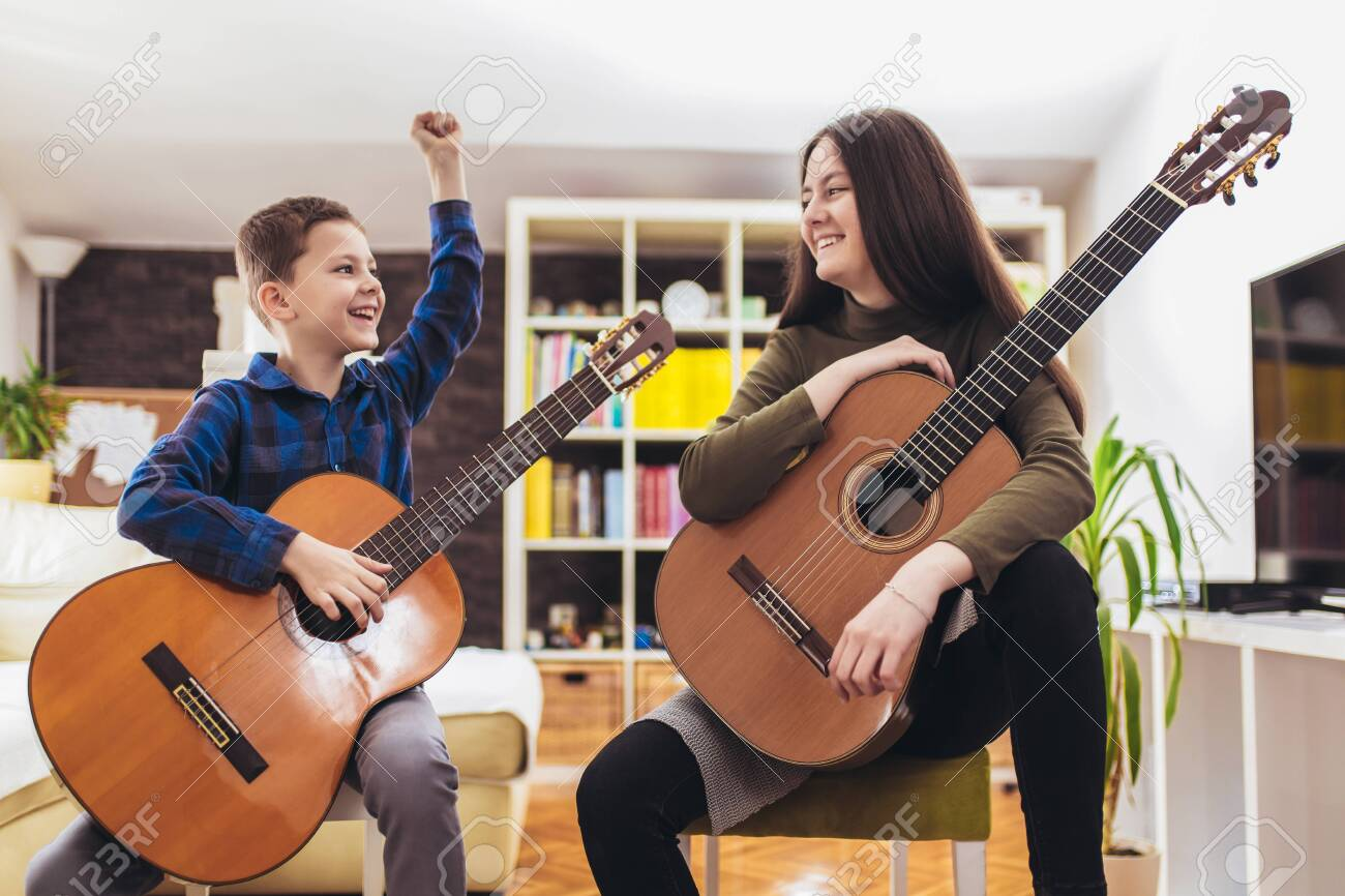 Brother and sister playing guitar at home and having fun. - 144137657