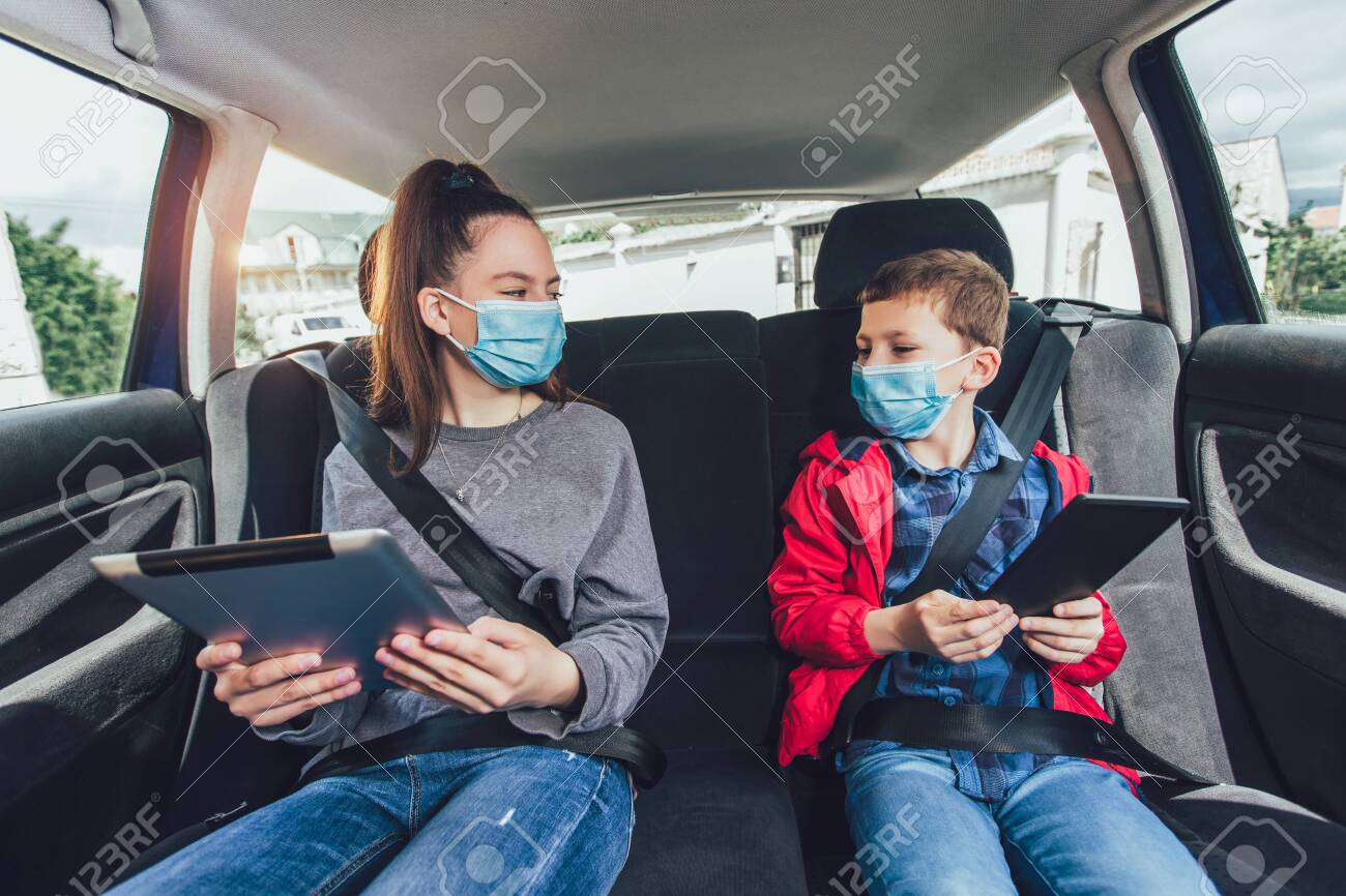Kids wearing anti virus masks and using digital tablets in the car. Kids are travelling in car during coronavirus outbreak - 150641437
