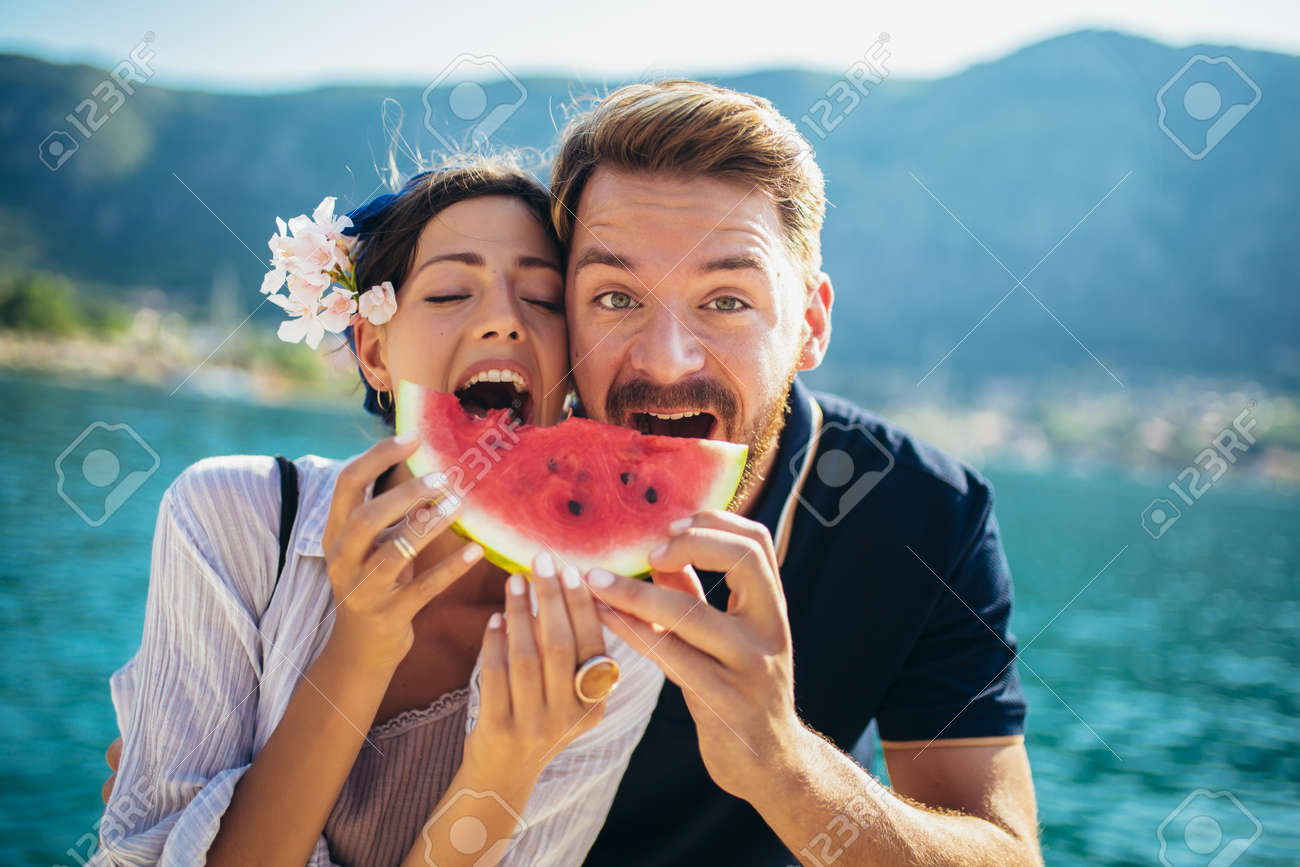 Young smiling couple eating watermelon on the beach having fun - 151968558