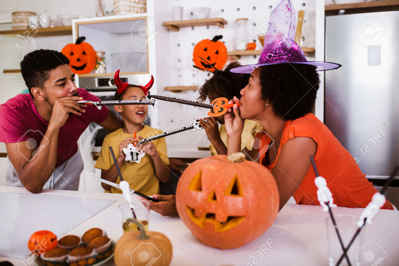Happy family mother father and children prepare for Halloween. They are carving pumpkin. - 155430873