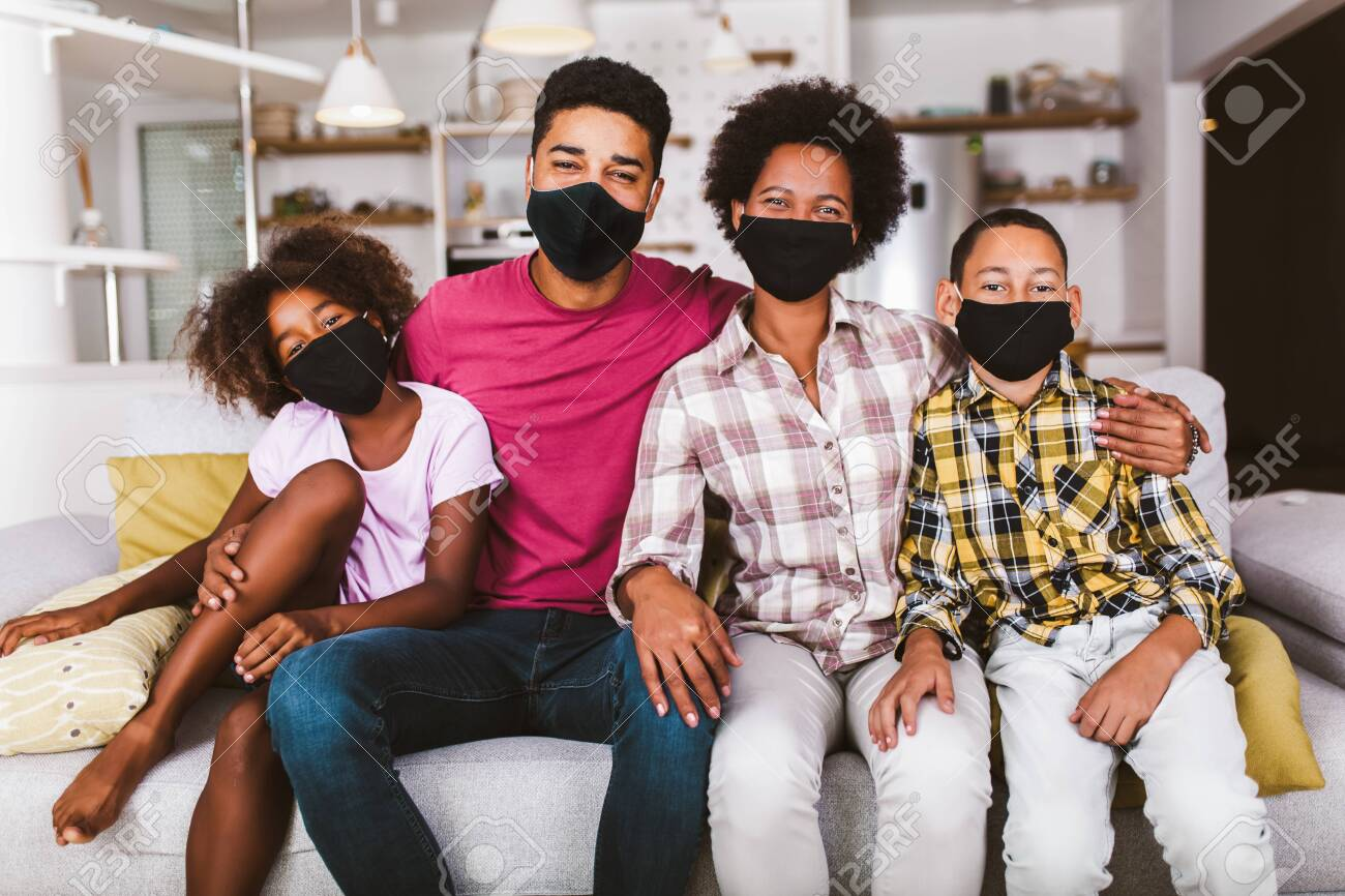 African American parents and cute small kids wearing protective masks at home. Stop the virus and epidemic diseases. - 155800071