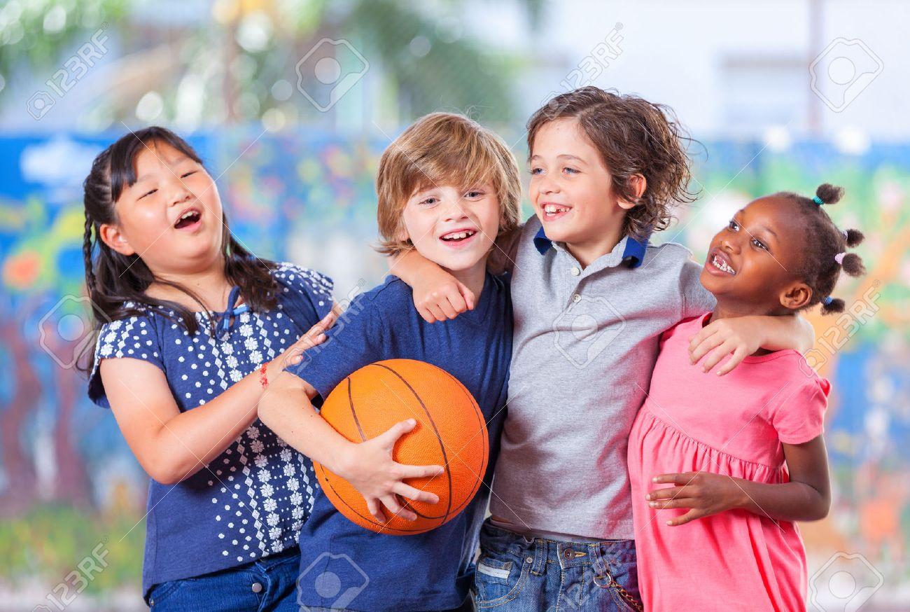 Des enfants heureux embrassant tout en jouant au basket. Concept de convivialité de l'école primaire. Banque d'images - 39870094