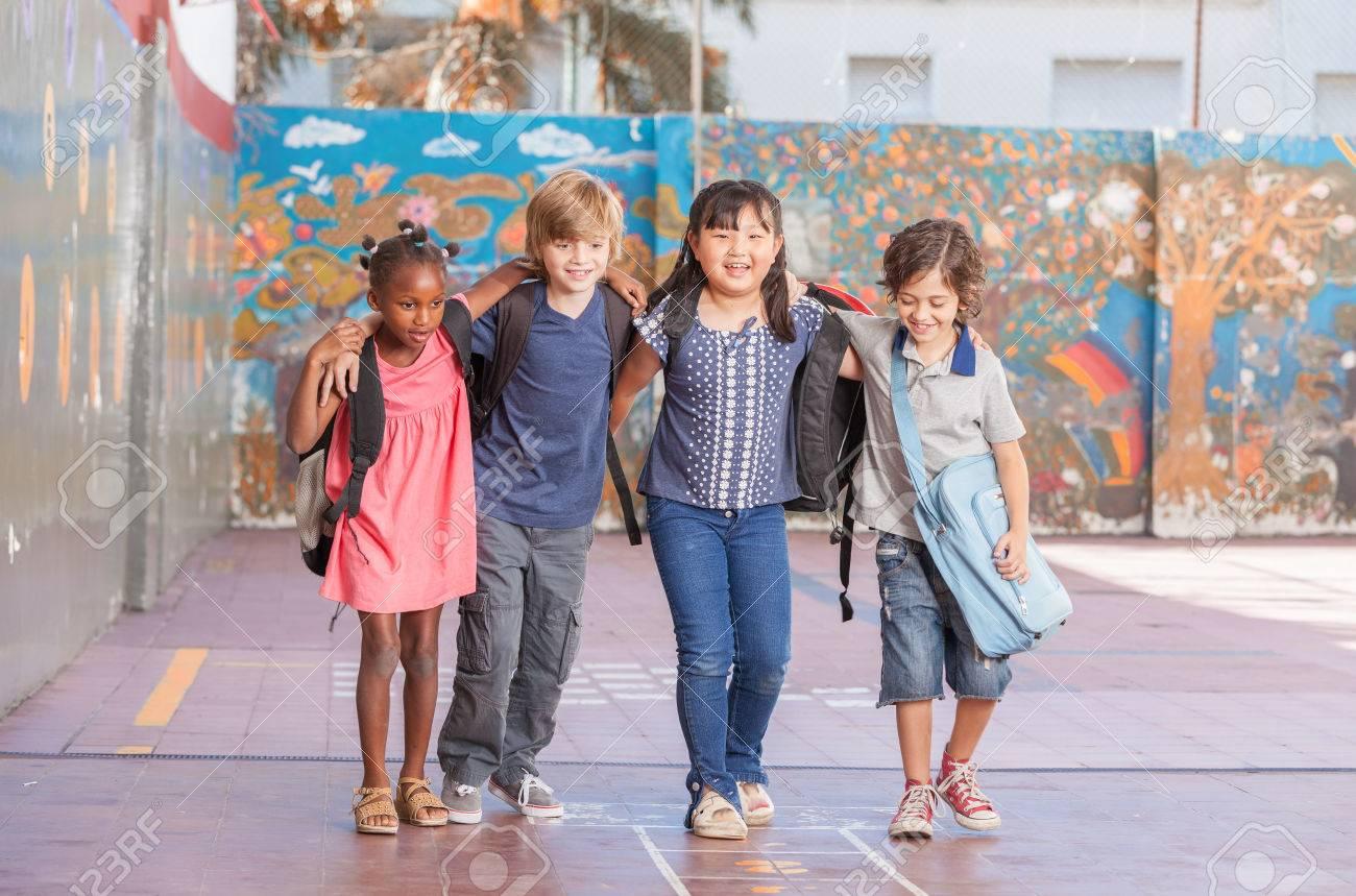 Des enfants heureux embrassant et en jouant à l'école multiculturelle. Banque d'images - 43038585