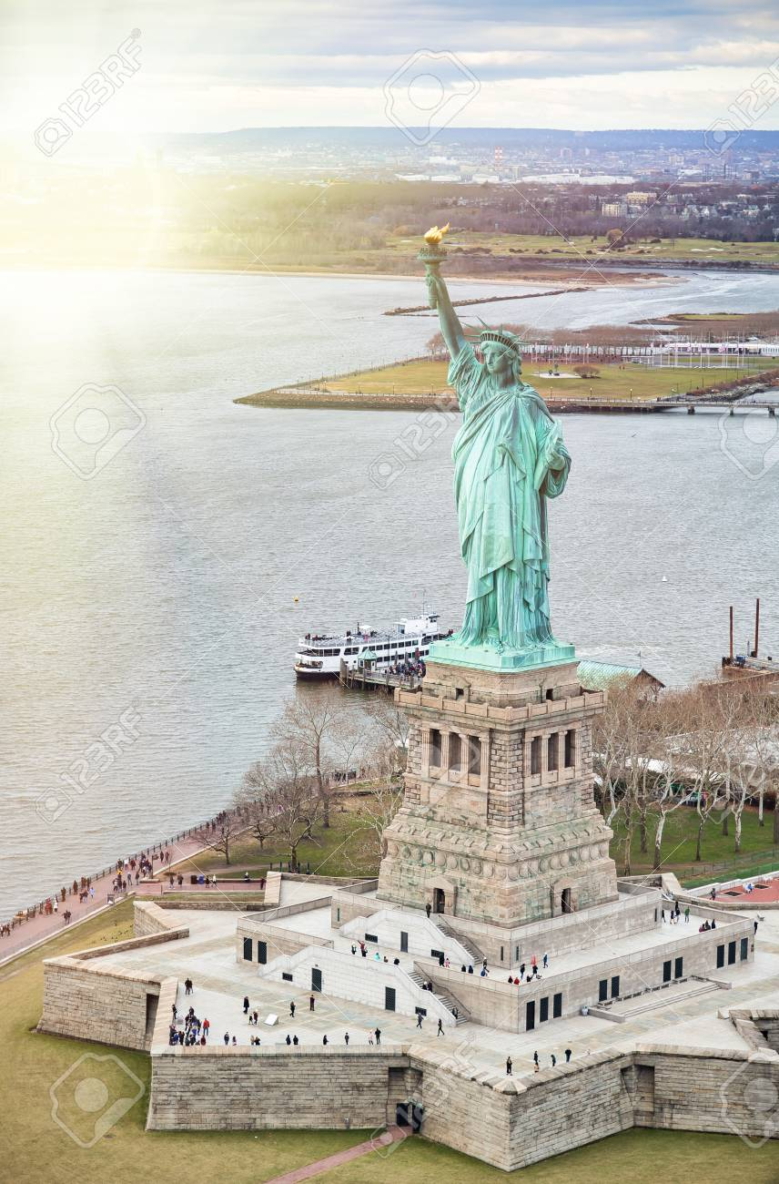 Statue Of Liberty On Liberty Island And Ferry Boat With Tourists
