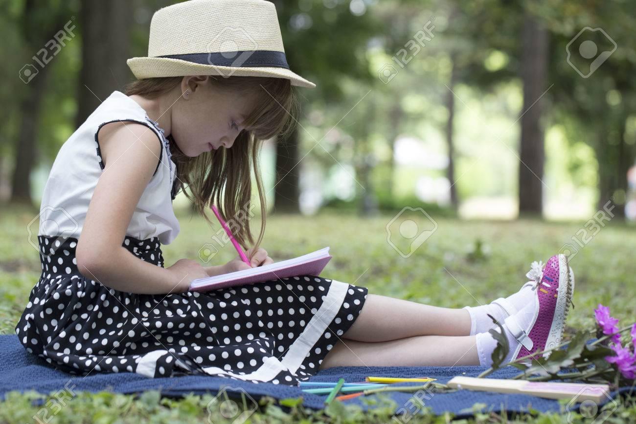 Petite Fille Mignonne Avec Un Chapeau Une Robe Se Trouve Dans La Nature Sur L Herbe écrit Et Dessine Dans Le Cahier