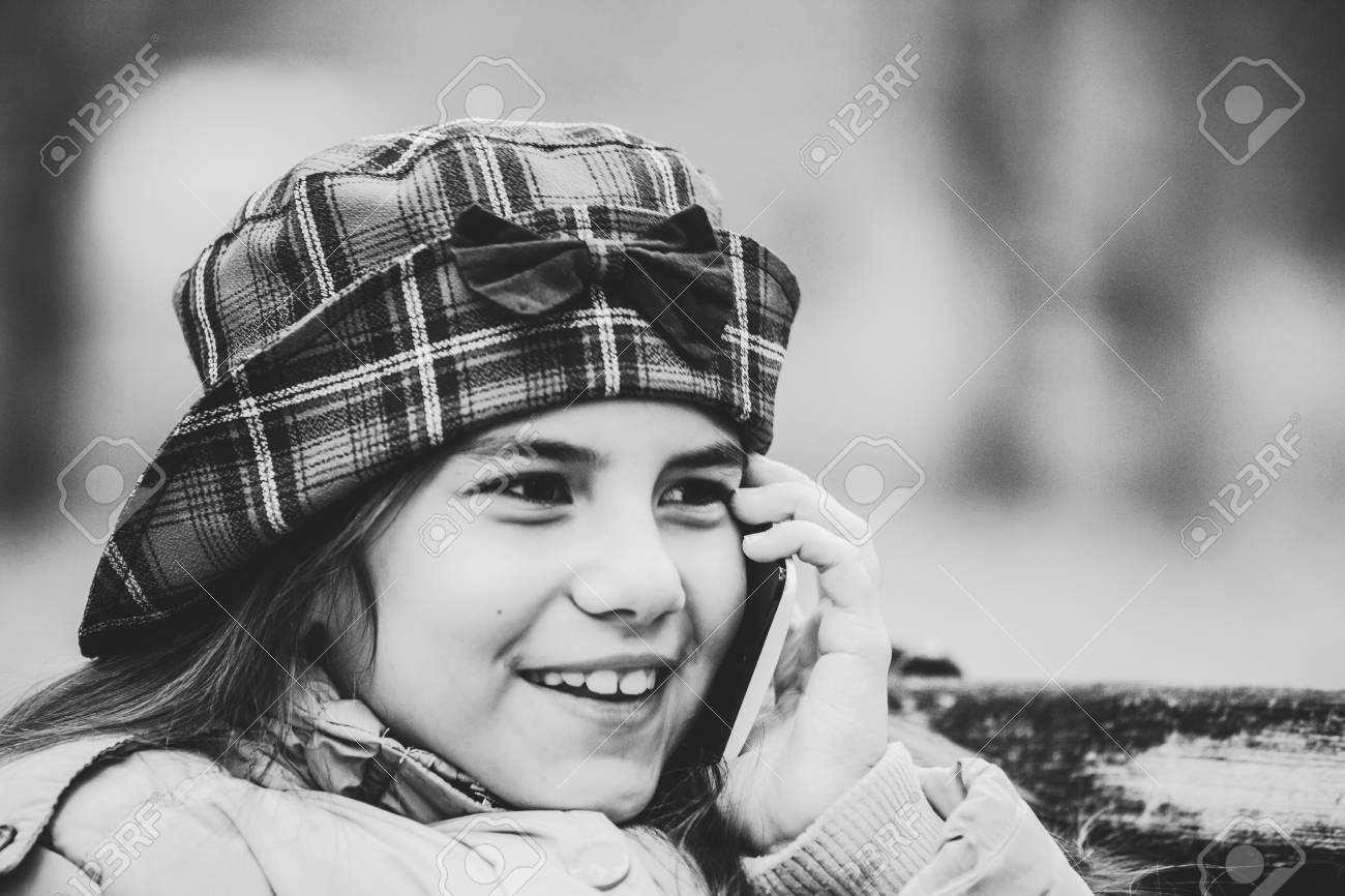 Black and white photo close up face shot of cute little girl with hat talking on smart phone outdoor