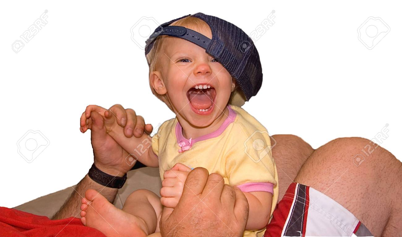 This young girl is yelling and laughing as she's playing on an adult's lap with a baseball cap, against a white background. Stock Photo - 5225919