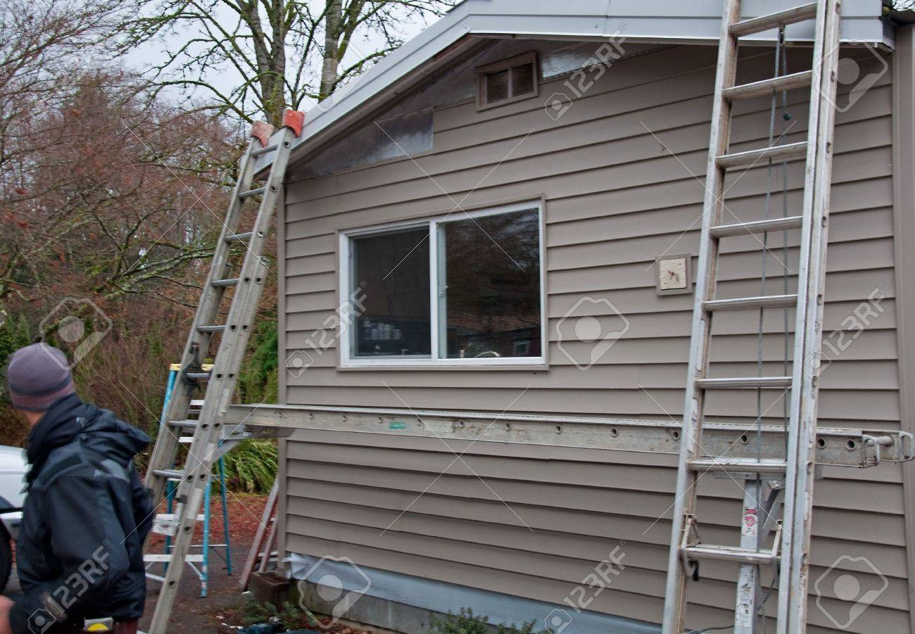 This exterior home renovation project has ladders and scaffolding in the midst of this project.  Construction worker is off to the side of this photo. Stock Photo - 6100849