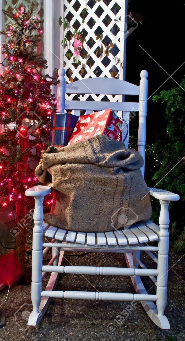 ein weißer schaukelstuhl mit einem sack von geschenken auf dem stuhl