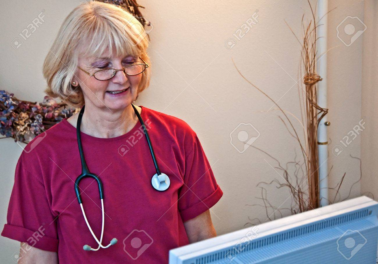 This older woman medical professional, doctor or nurse, is wearing a stethoscope while running a medical equipment machine in a medical setting office Stock Photo - 16964212
