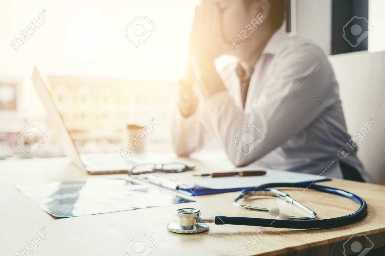 Stethoscope and doctor sitting with laptop stress headache about work in hospital - 86044479