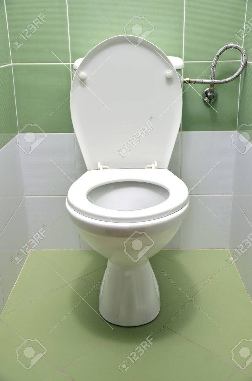 Flush Toilet With White And Green Tiles In Background, Front.. Stock ...