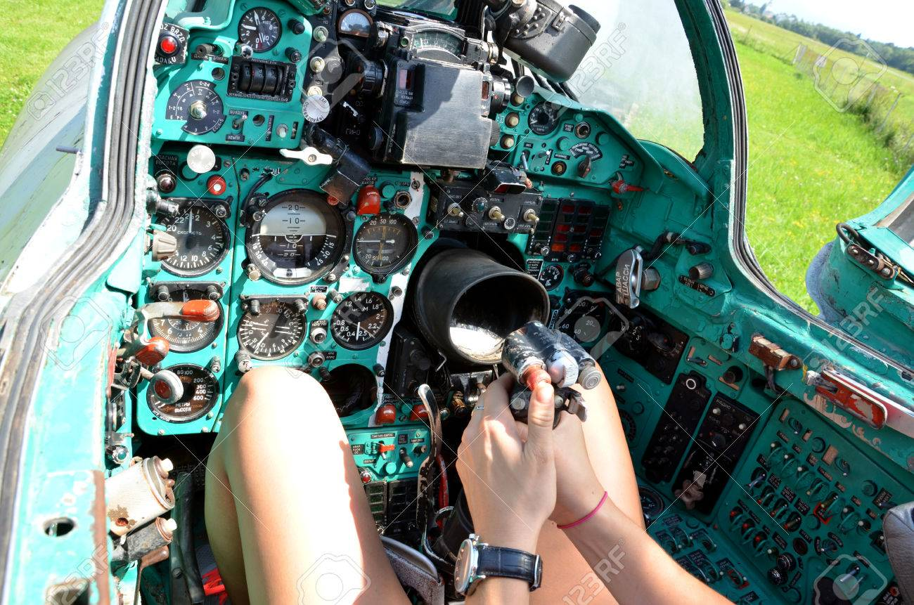 Girl sits in cabin of old jet fighter MiG-21 holding the control