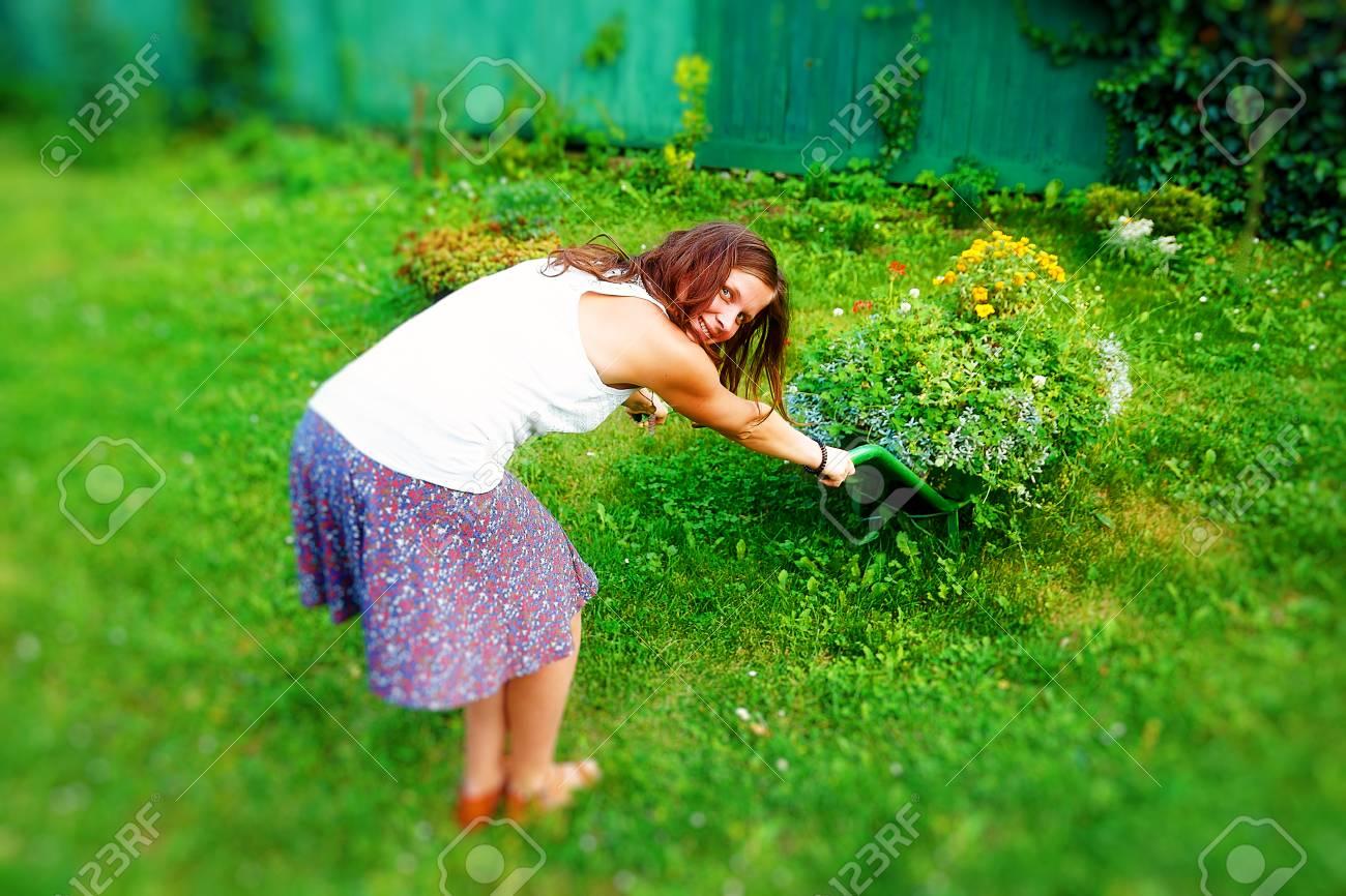 Young Woman In Garden Playfully Pushing Decorative Wheelbarrow ...