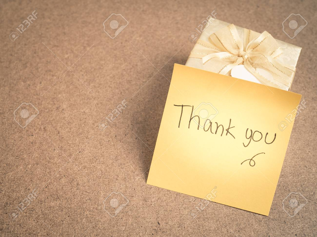 hand writing thank you words on yellow sticky note with gold