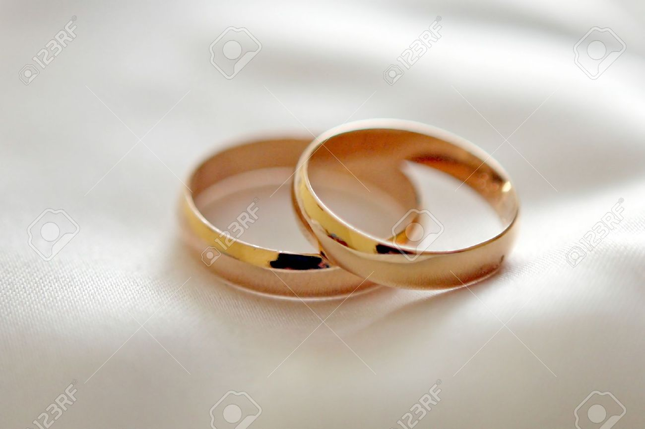 Two Wedding Rings With White Flower In The Background Wedding