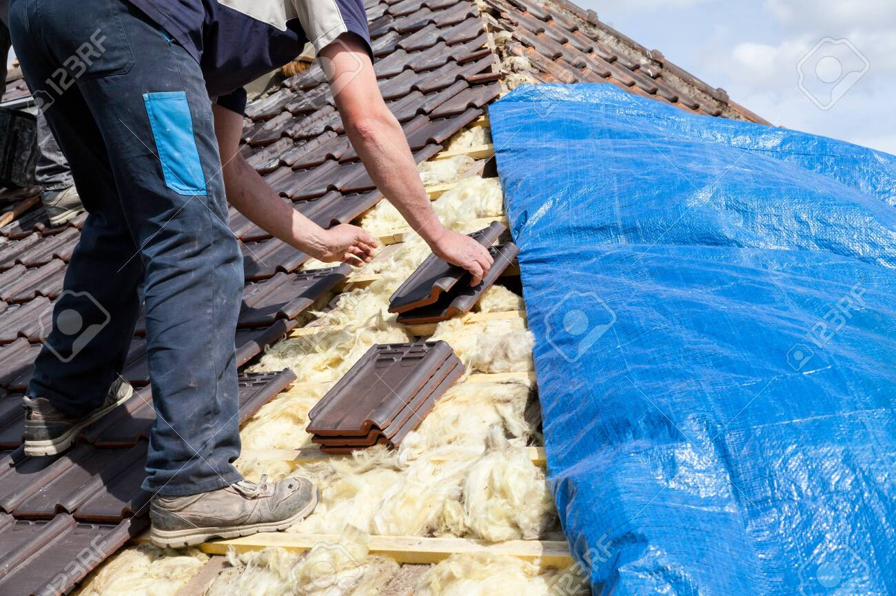 a roofer laying tile on the roof - 135418114