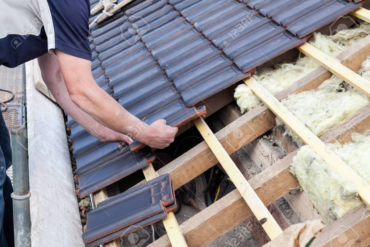 a roofer laying tile on the roof - 135418116