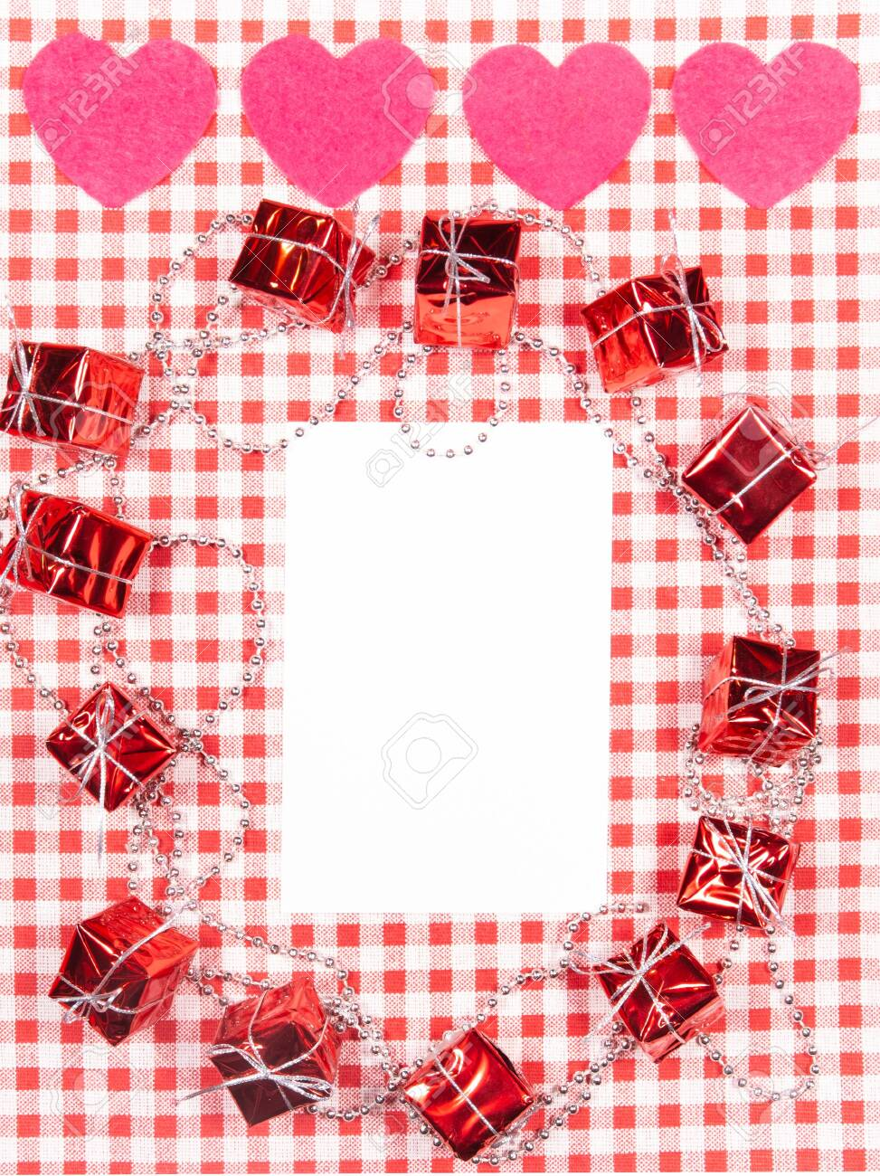background with red and white Vichy fabric for Valentine's day with pink hearts, small gifts, garlands of small pearls and a white card to put the text. valentines day concept - 138175493