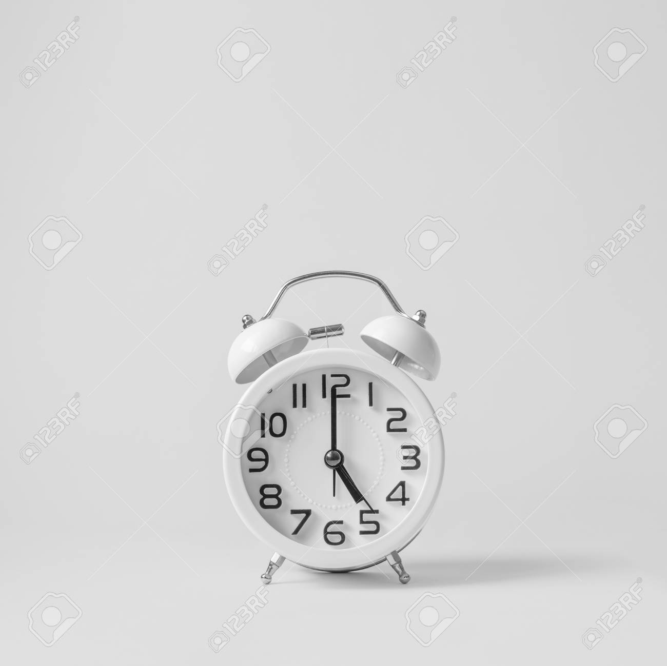 White vintage alarm clock on white background. Concept get off work at five. - 122874643