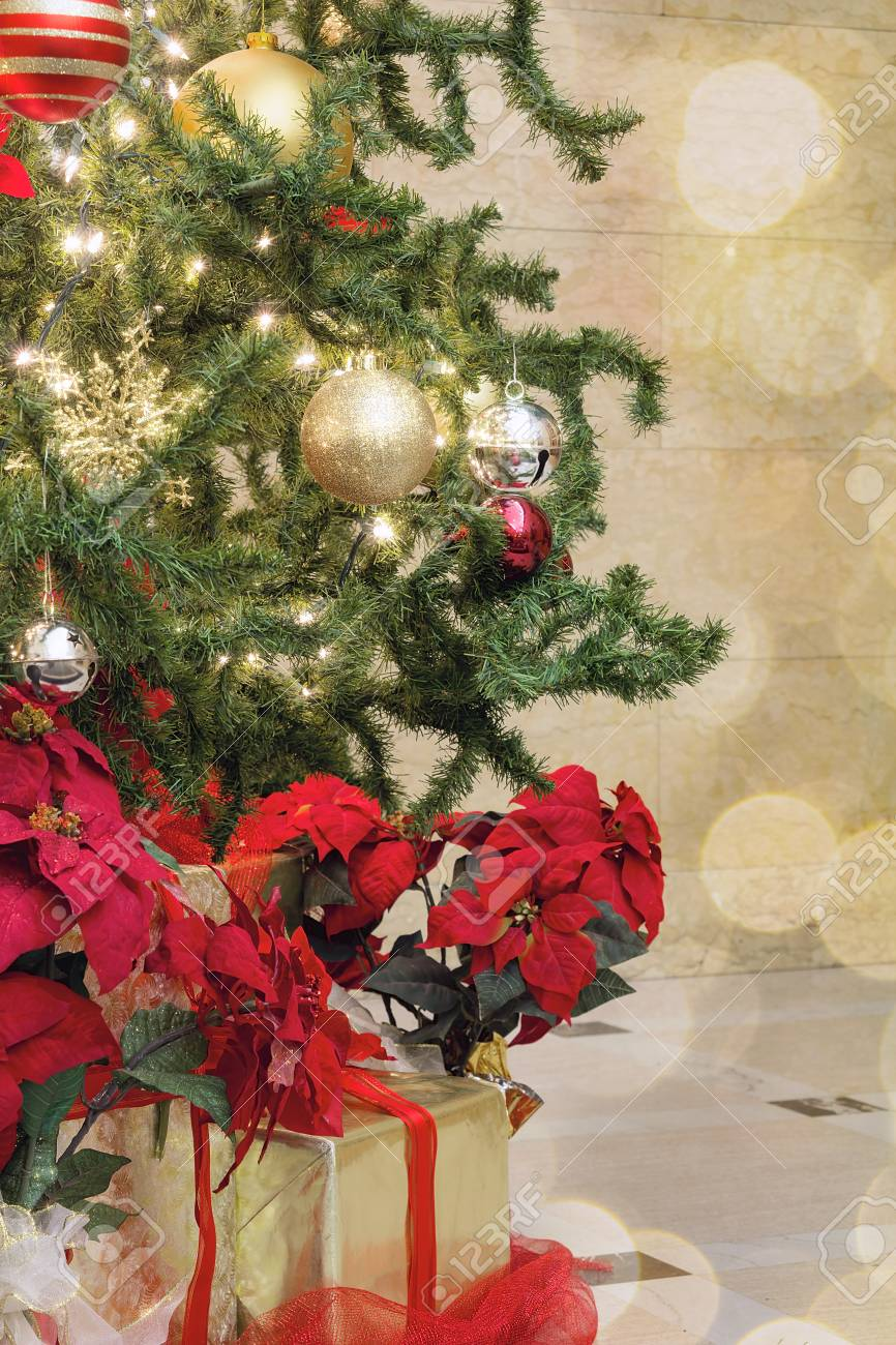 christmas tree decoration with bokeh lights sparkles ornaments ribbons poinsettia and presents under the tree stock