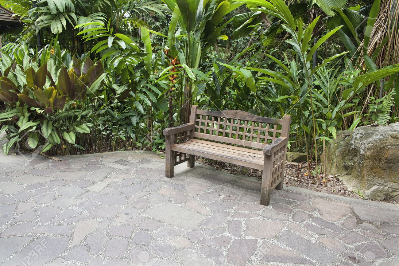 Stock Photo   Wood Bench In Tropical Garden With Stone Paver Patio