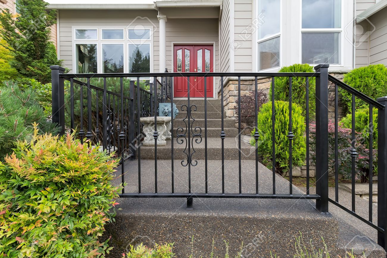 House Front Entrance With Wrought Iron Railings On Stairs With
