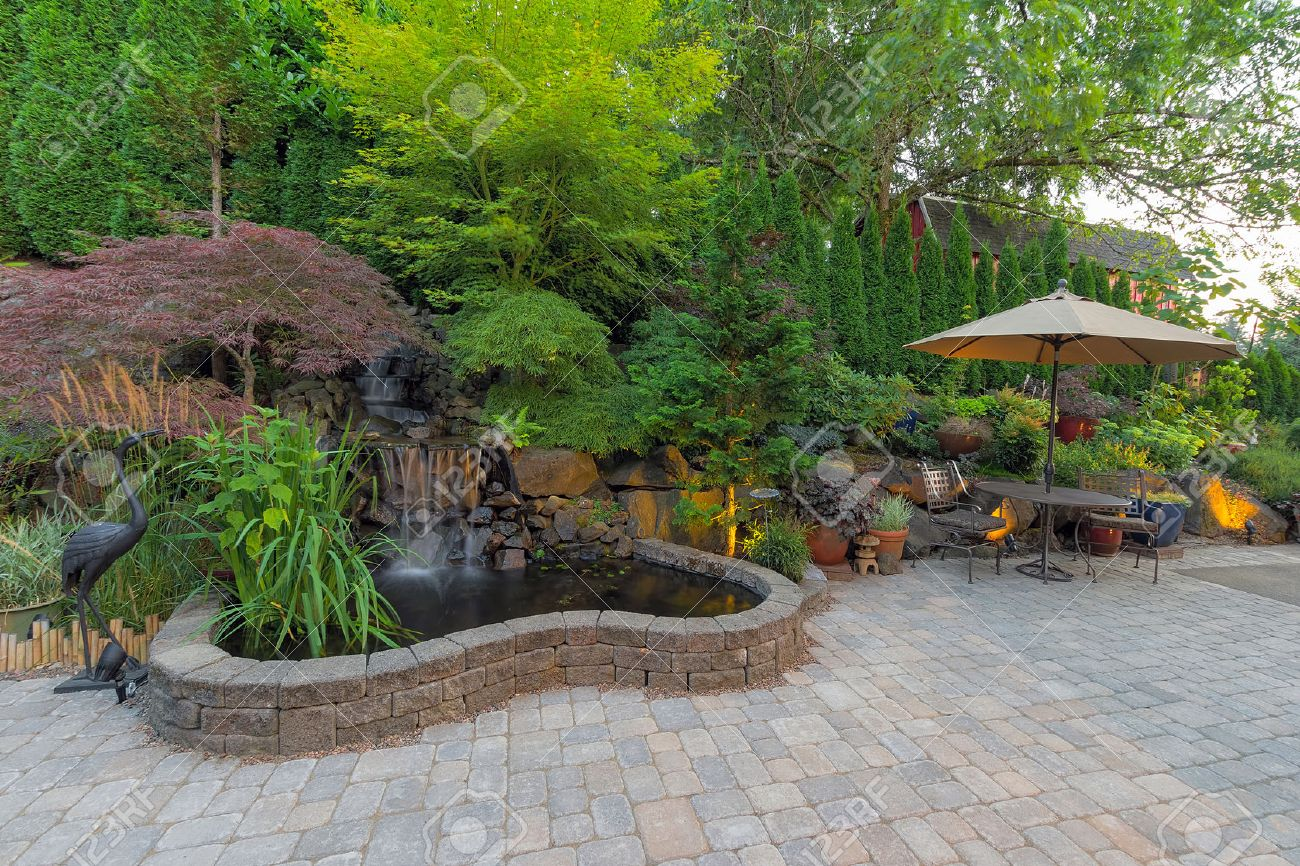 123RF.com & Backyard Garden landscaping with waterfall pond trees plants..