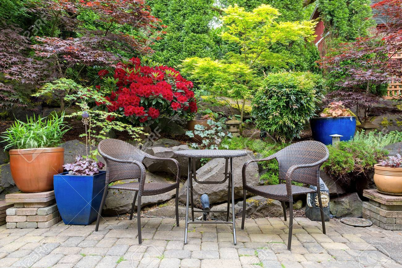 Garden backyard with lush plants landscaping and stone paver patio hardscape with wicker bistro furniture chair and table set in spring season - 79264439