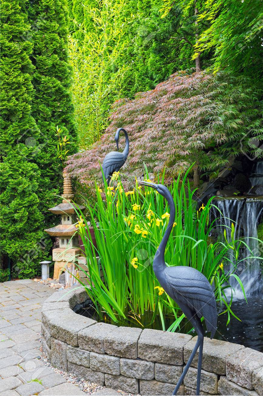 japanese inspired backyard home garden with bronze cranes stone