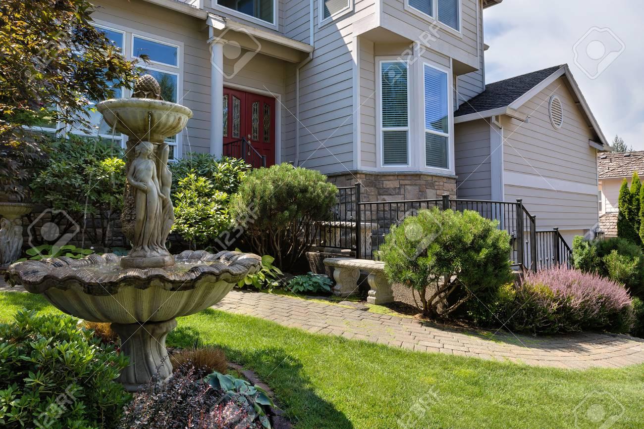 Maison unifamiliale dans la banlieue nord-américaine avec jardin aménagé,  banc de promenade en brique verte et fontaine en pierre