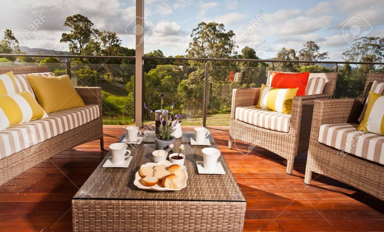 Cómodo Muebles De Mimbre Al Aire Libre Con Cojines A Rayas En Una Terraza De Madera Con Vistas A Un Jardín Con Una Mesa Baja Para El Té Y Las Galletas