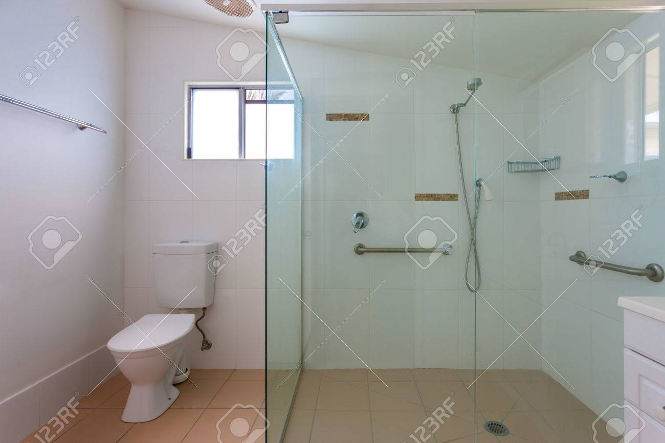 Salle de bains simple avec une grande cabine de douche avec des murs en  verre et poignées de soutien