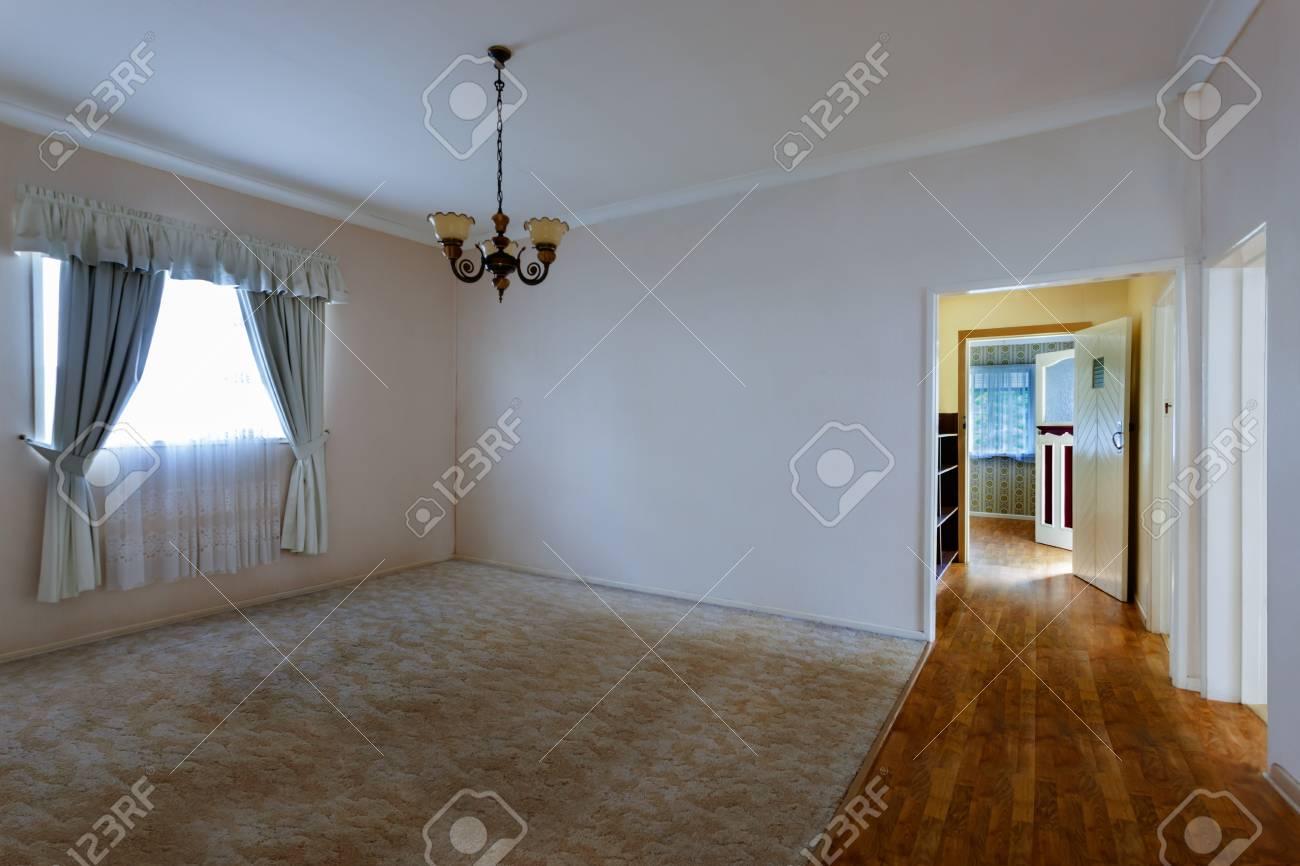 Sala de estar vacía o posiblemente comedor solo con cortinas en la ventana
