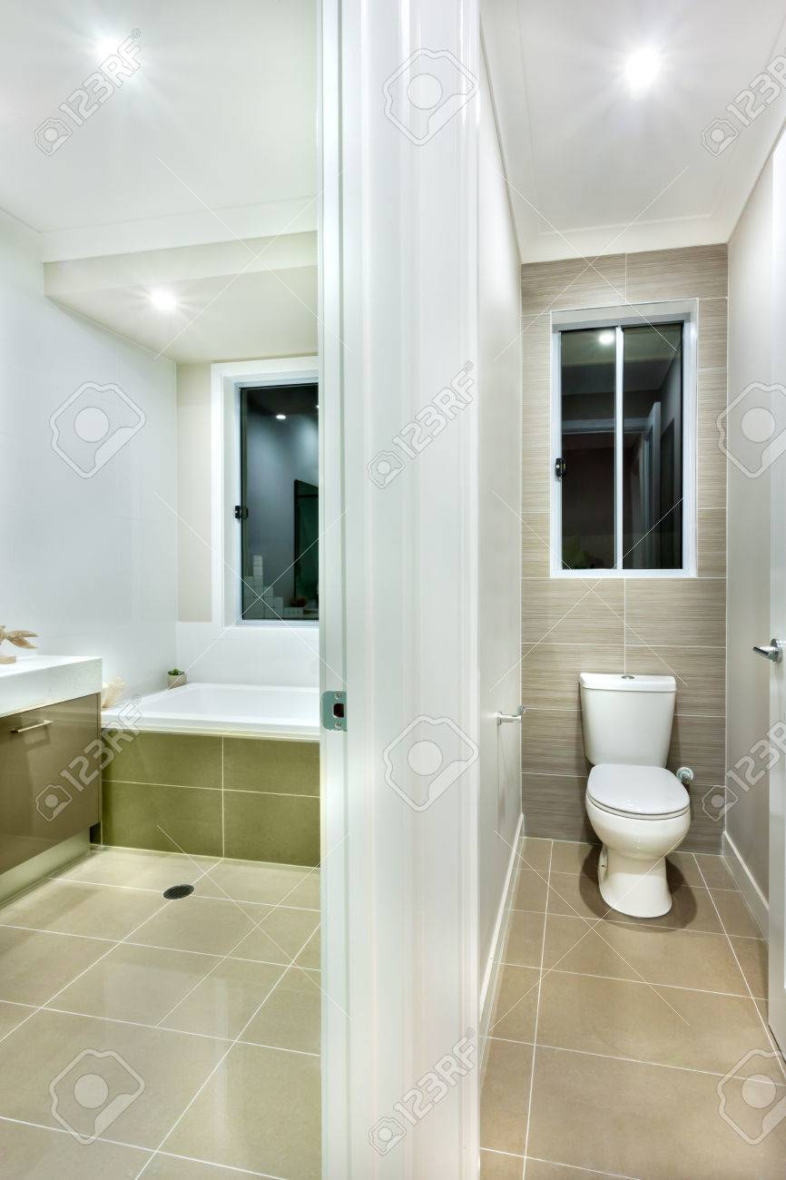 The Toilet Has Dark Color Tiles And A Glass Window Over The White ...