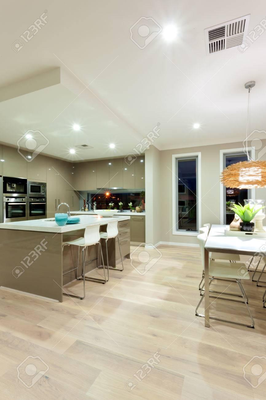 Palazzo moderno dispone di una cucina oltre ad un tavolo da pranzo e più  spazio con pavimento in legno. Ci sono sedie bianche di tutto il piano di  ...