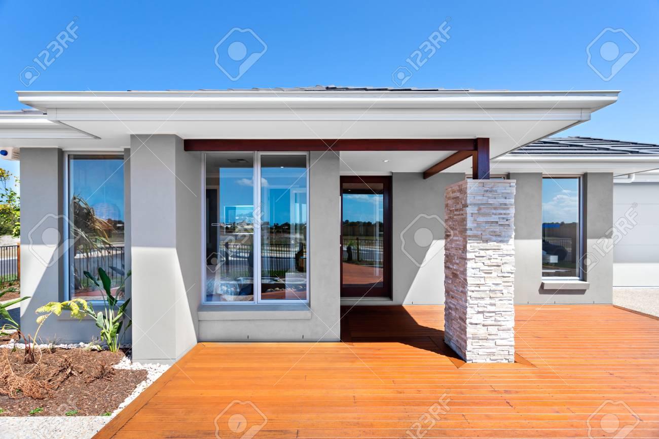 Ingresso Casa Esterno In Pietra davanti a una casa moderna con cortile in legno. il tetto è detenuto da  forti travi con mattoni e pilastro di pietra. la casa ha almeno quattro
